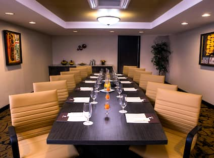 Water Pitchers, Drinking Glasses, Note Pads, and Seating For 12 at Boardroom Table