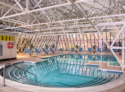 Indoor Pool Surrounded by Blue Loungers and Windows