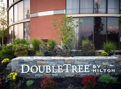 Detailed View of Signage, Landscaping, and Hotel Exterior
