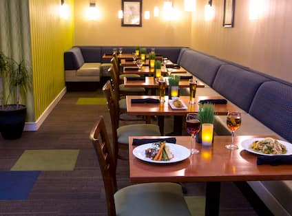 Tables With Place Setting, Chairs, and Booth Seating in Restaurant Dining Area