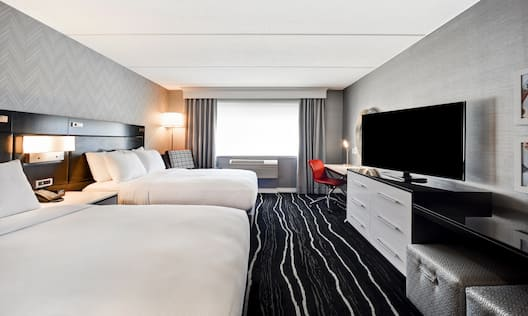 Guest Room with Two Queen size Beds HDTV and Work Desk