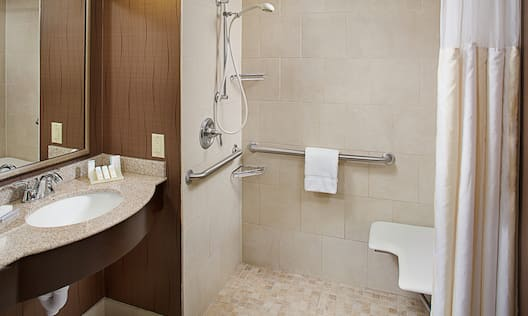 Accessible Guest Bathroom Vanity with Amenities and Roll-In Shower with Bench