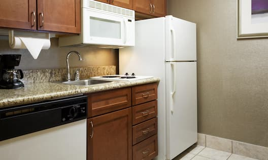 Kitchen with full-size refrigerator, dishwasher, sink, and microwave oven.
