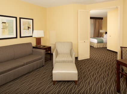 Accessible Suite Living Room Area With Wall Art Above Sofa, Side Table With Lamp, Arm Chair With Ottoman, Open Doorway to Bedroom, and Dining Table With Seating for Two
