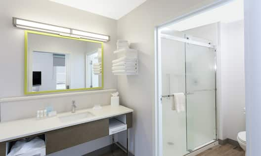 Bathroom Vanity Area with Mirror and a Shower with Sliding Doors
