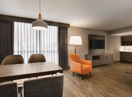 Lounge area in suite with chair, table and TV