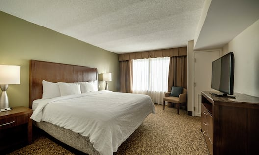 King Bed, Armchair, and TV in Junior Suite Bedroom