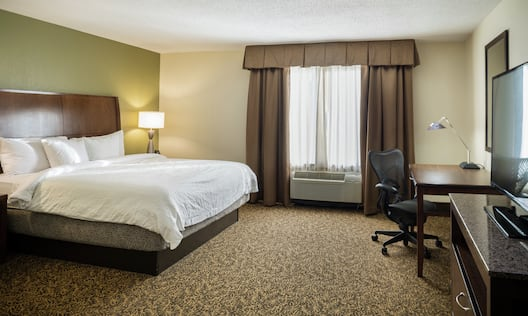 King Bed, Window With Long Drapes, Work Desk,and TV in Guest Room