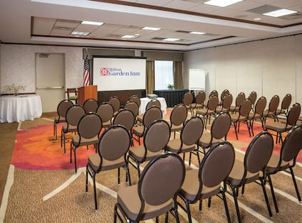 Meeting Room Arranged Theater Style With Rows of Chairs Facing Projector Screen and Podium