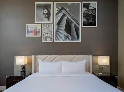 King Guestroom Executive Floor with bed, lamps and wall art above bed.