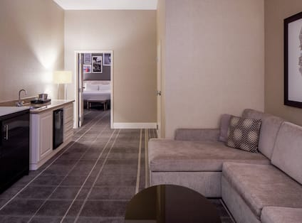 One Bedroom King Suite with large sofa, wet bar, and TV.