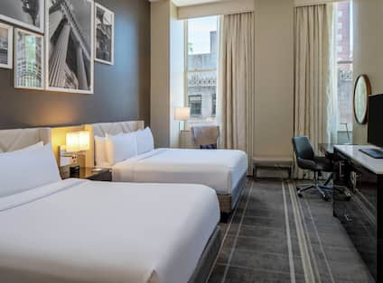 Deluxe Double Queen Guestroom with TV, desk and large windows.