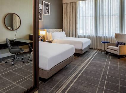 Deluxe Double Queen Hearing Accessible Guestroom with full sized mirror sitting chair and desk reflection.