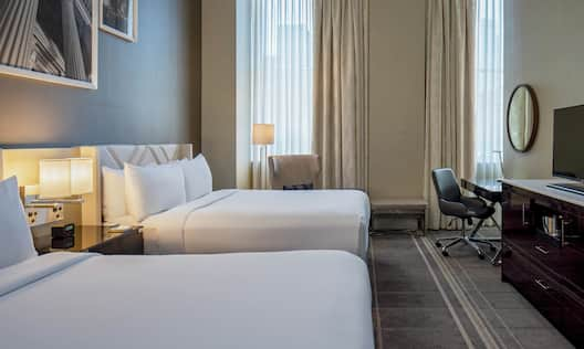 Double Queen Guestroom Executive Floor with  large windows, TV and desk.