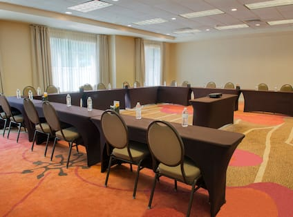 Meeting Room With Bottled Water on U-Shaped Table, Chairs, and Projector Table