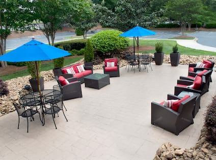 Tables With Umbrellas, and Soft Seating on Patio by Parking Lot