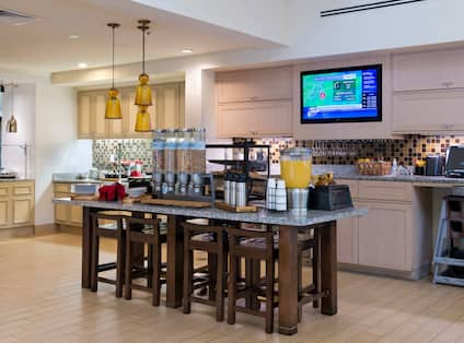 Hot and Cold Buffet Selections in Breakfast Area With Plates, Utensils, and Beverages