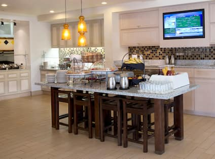 Pastries and Beverages on Large Table in Breakfast Area