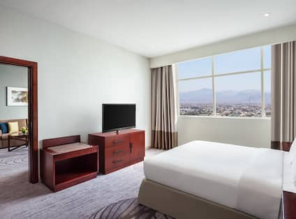 Deluxe Suite Bed View with Lounge Area in Background