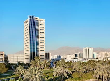 Exterior view of hotel with palm trees in foreground