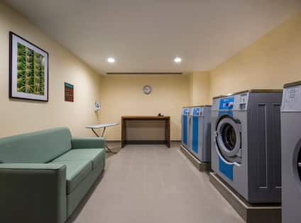 Coin Operated Washing and Drying Machines, Green Sofa and Folding Table in Laundry Facility