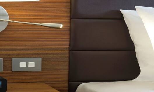 Bedside Table With Clock, and Illuminated Lamp by Neatly Made Bed in Accessible Room