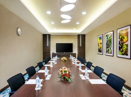 Seating for 12 atTable in Al Khor Meeting Room With TV and Wall Art