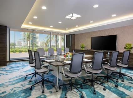 Seating for 10 at Square Boardroom Table Facing Large TV in Al Nakheel Meeting Room