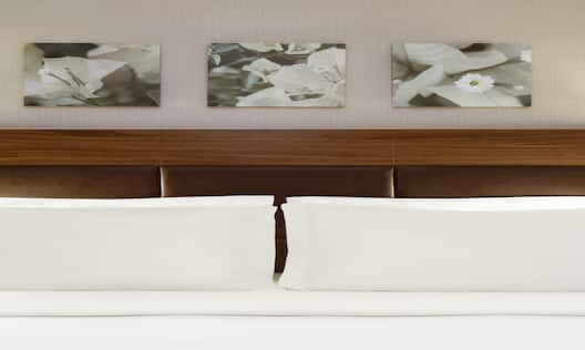 Wall Art Above Neatly Made King Bed Between Two Illuminated Lamps and Bedside Tables