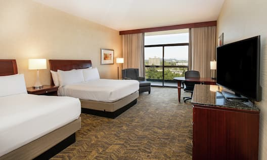 Two white beds and a television in a guest room