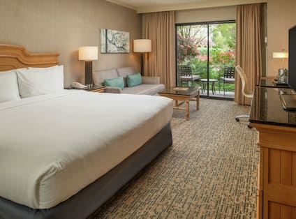 White bed in a hotel room with lounge area and outside view