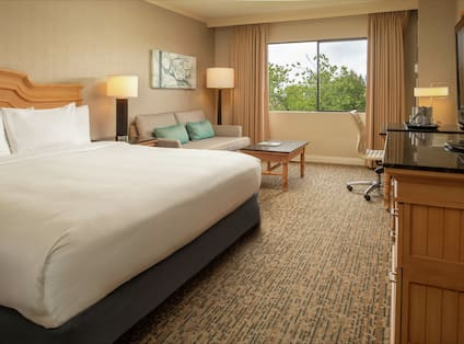 White bed in a hotel room with an outside view