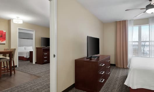 Suite Bedroom with King Bed, Television and Entry to Living Room and Second Bedroom