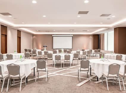 Meeting Room Setup with Round Tables and a Projection Screen
