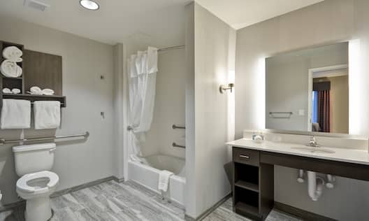 Toilet With Fresh Towels and Grab Bars, Bathtub With Grab Bars, Large Vanity Mirror, Sink and Toiletries in Accessible Suite Bathroom