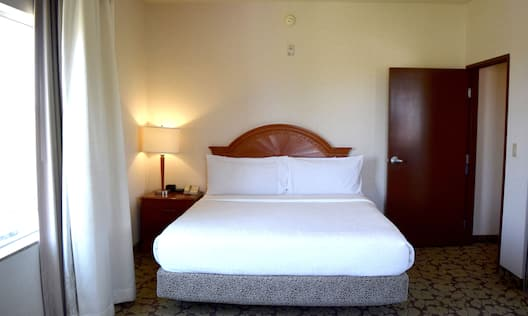 King deluxe one bedroom suite, hearing accessible bed with white linens.