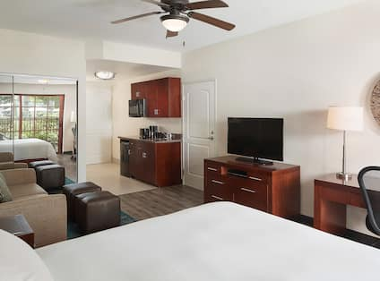 Bed in room with TV, couch and kitchen