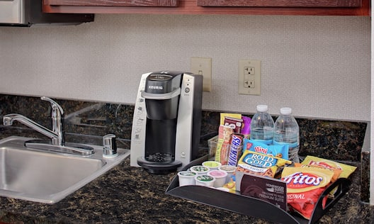 Premium suite snacks on kitchen counter next to Keurig machine and sink