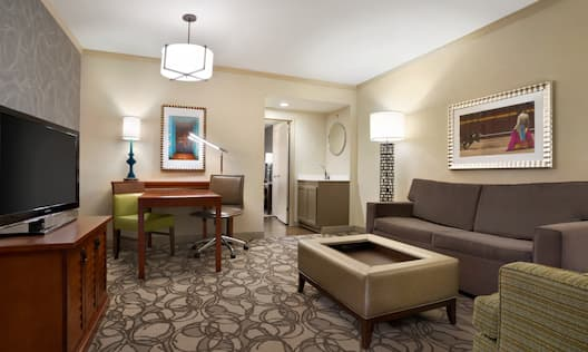 Suite Living Room with Lounge Seating, Work Desk, Television, Wet Bar and Entry to Bedroom