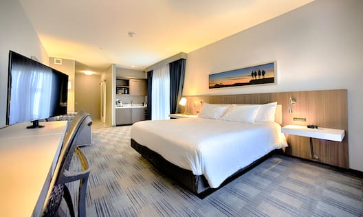 Large Bed in Guest Room with HDTV Desk and Wet Bar Area