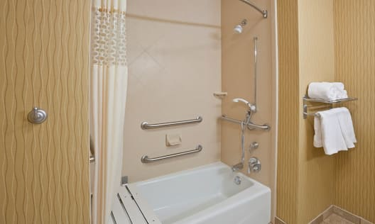 Bathtub With Grab Bars, Seat, and Handheld Showerhead in Hearing Accessible Bathroom