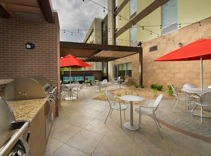 Outdoor Patio Seating Area with Chairs, Tables, Umbrellas and BBQ Grill