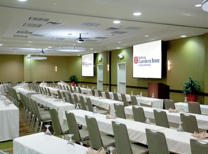 Classroom Setup in Balloom With Tables and Chairs Facing Two Presentation Screens and a Podium