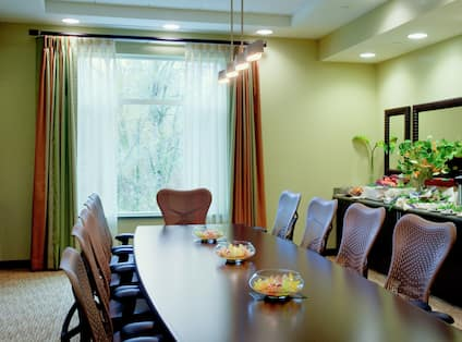 Wall Art, Window With Open Drapes, Wall Mirror Above Refreshment Station, and Boardroom Table With Flowers