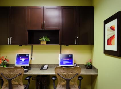 Business Center With Wall Art, Cabinets Over Two Computer Workstations, and Ergonomic Chairs