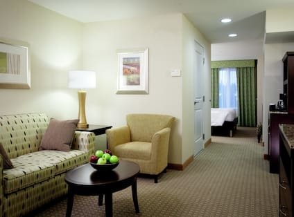 Bowl of Apples on Coffee Table, Wall Art Above Sofa, Illuminated Lamp on Side Table, Armchair, Open Doorway to View of Bedroom, Hospitality Center, and TV in Suite Living Area