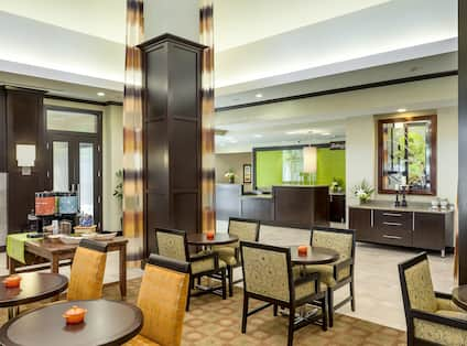 Tables, Chairs, Beverage Station, Long Drapes, and View of Front Desk in Lobby