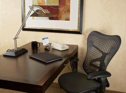 Wall Art Above Spacious Work Desk With Illuminated Lamp, Phone, and Ergonomic Chair