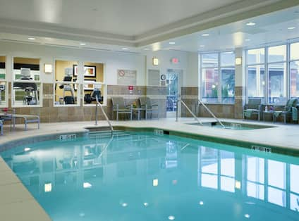 Indoor Salt Water Pool and Whirlpool With Loungers, Chairs, Glass Door, and Large Windows With View Into Fitness Center