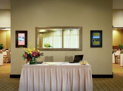 Two Chairs, Flowers, and Laptop on Registration Table With White Linens, and View into Meeting Space With Classroom Set Up